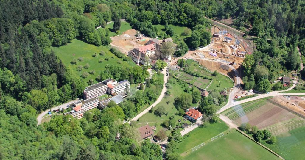 Das Areal des Kartäuserklosters in Freiburg: Unten in der Mitte der Meierhof, links oberhalb das Seniorenheim aus den 70er Jahren, in der Mitte oberhalb das alte Kloster und rechts neben dem Kloster die Baustellen für die Betonwürfel des UWC (Luftaufnahme vom 18.05.2014: Dr. W.-D. Winkler)